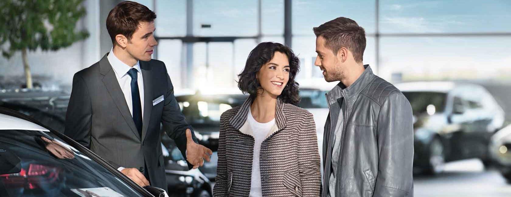 Mann erklärt das BMW Abo einem jungen Paar.
