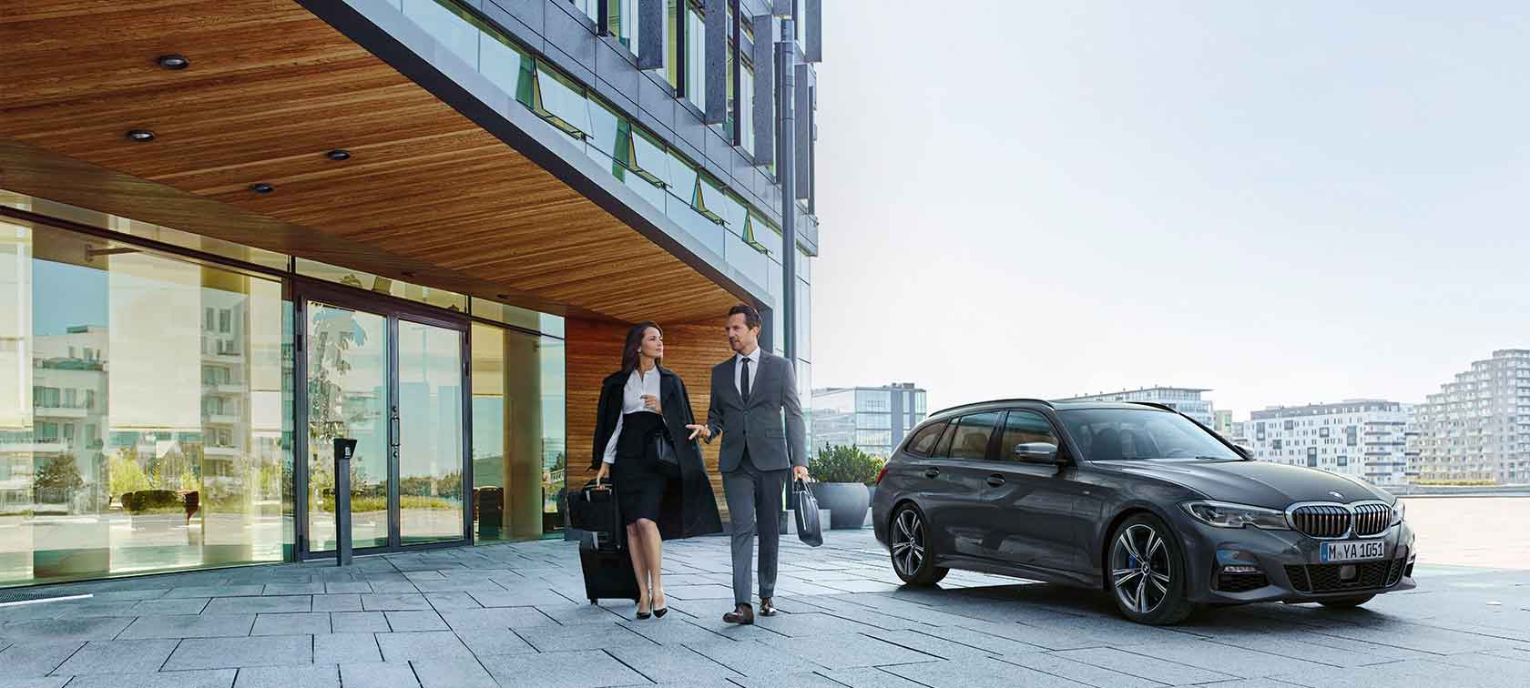 Young woman and partner go on a business trip with the BMW subscription.